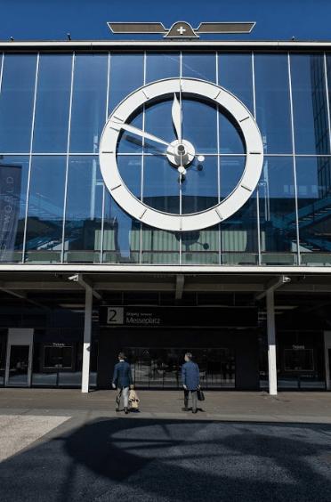 Personas entrando a un edificio con un reloj grande en color blanco