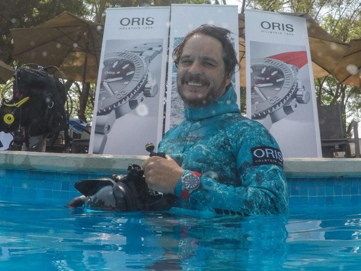 Gerardo dentro de una alberca con traje azul utilizando un reloj Oris