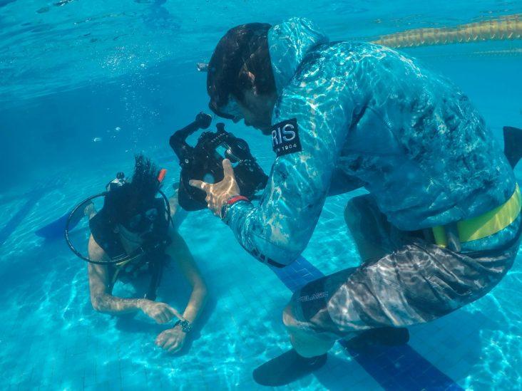 Hombres bajo el agua en una alberca tomando fotografías