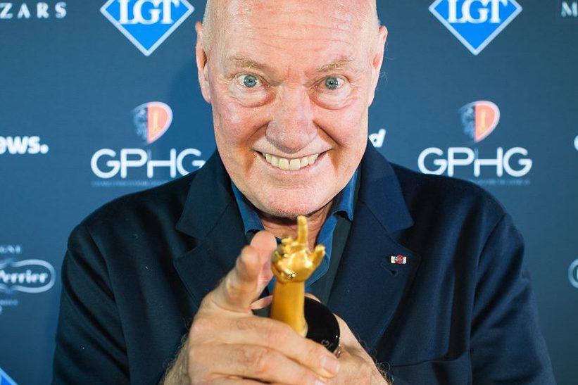 Jean-Claude con saco y camisa azul sosteniendo un premio en las manos