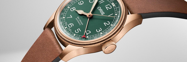 Reloj Oris verde con correas y detalles en color bronce