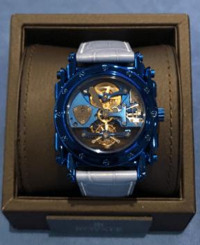 Reloj con correas azul claro y caratula en azul fuerte con engranajes al centro en dorado