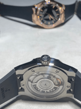 Reloj con correas en color negro y detalles en bronce