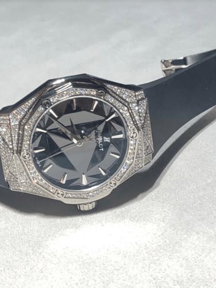 Reloj con correas en color negro y diamantes al rededor de la caratula