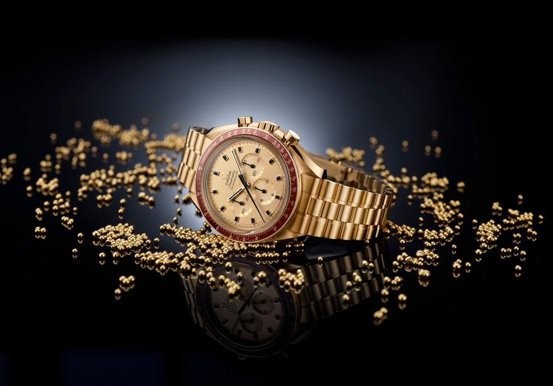 Reloj en color oro con detalles en rojo sobre pequeñas bolitas en color oro