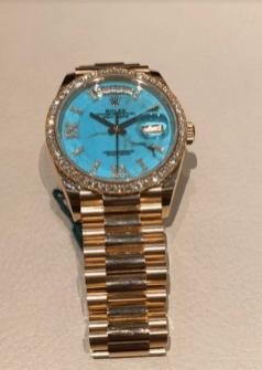 Reloj Rolex en color dorado con detalles en color azul agua