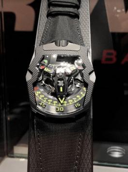 Reloj con correas negras de lona y caratula en negro con detalles en verde