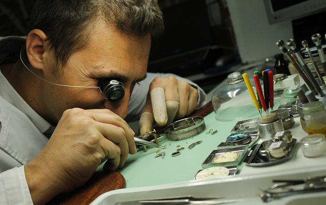 Hombre con varios instrumentos sobre una mesa para una cuidadosa reparación de un reloj