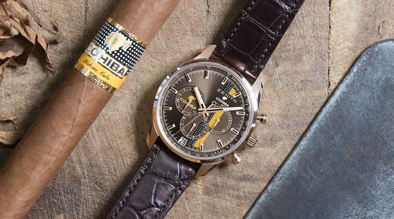 Reloj Cohiba México precio con correas en color café y carátula en color dorado junto a un puro