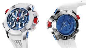 Reloj en color blanco con detalles en color dorado y la cartula en color azul con rojo visto de frente y detrás