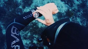 Imagen de un reloj en una mano bajo el agua