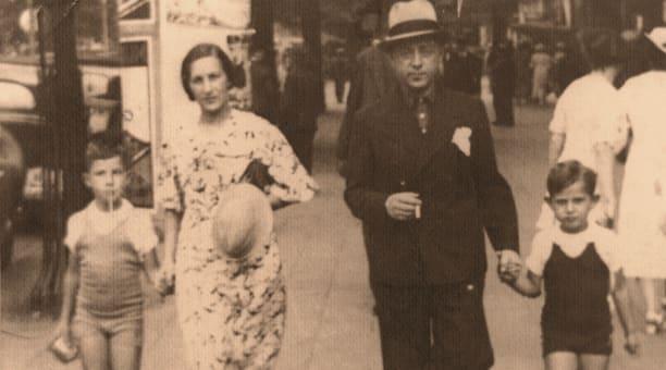 Hombre y mujer caminando en la calle tomando a sus hijos de la mano