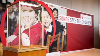 Collar Bvlgari Save The Children dentro de una vitrina y al fondo una lona con la imagen de niños sonriendo