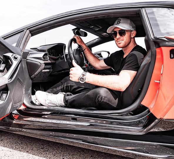 Hombre vestido de negro con lentes y gorra blanca sentado dentro de un carro