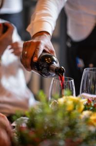 Persona sirviendo vino en una copa de cristal