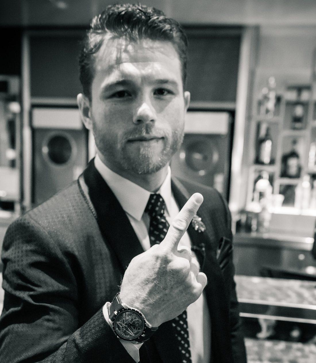 Canelo con saco, corbata y camisa blanca mostrando su reloj