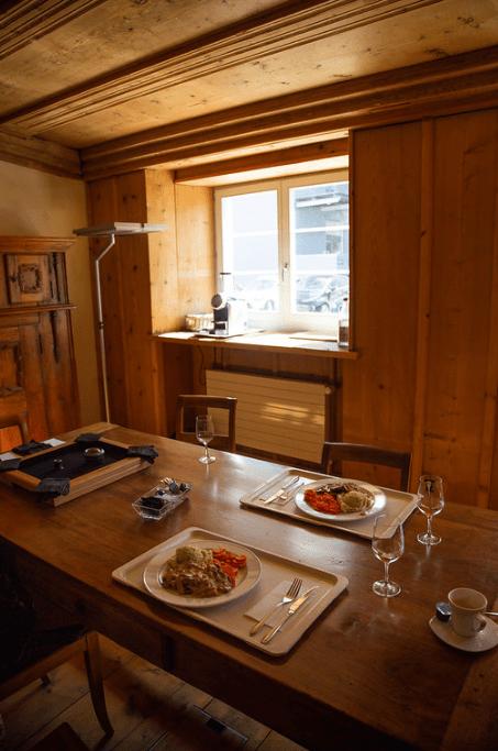 Platillos y copas sobre una mesa de madera dentro de una casa con estructura de madera