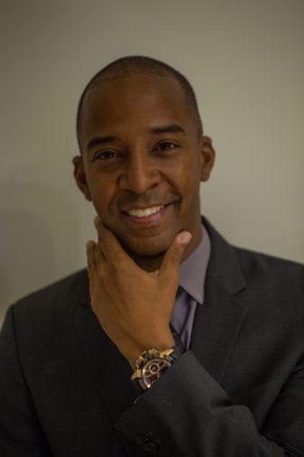 Dwayne Grannum con saco y corbata en negro y camisa azul de frente