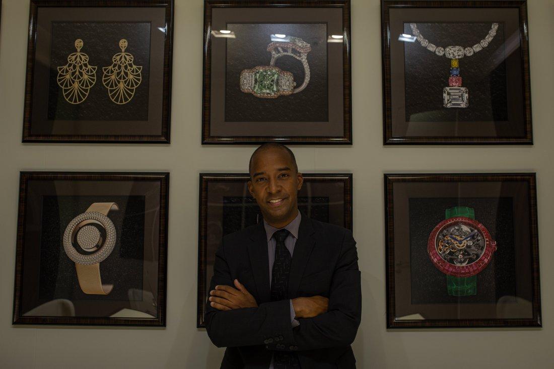 Dwayne Grannum con saco y corbata en negro y camisa azul y al fondo cuadros de diferentes joyas