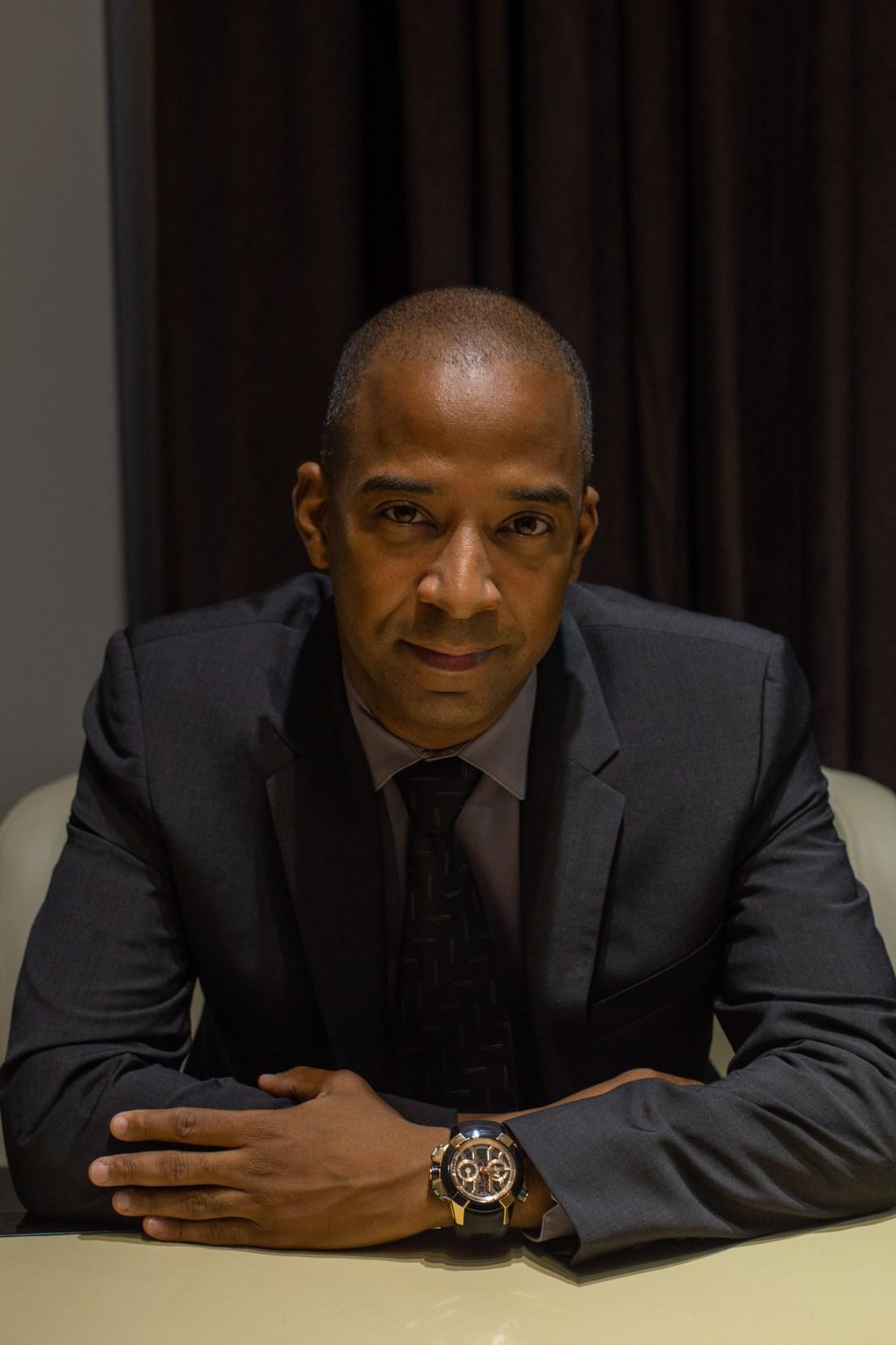Dwayne Grannum con saco y corbata en negro y camisa azul sentado recargado en una mesa
