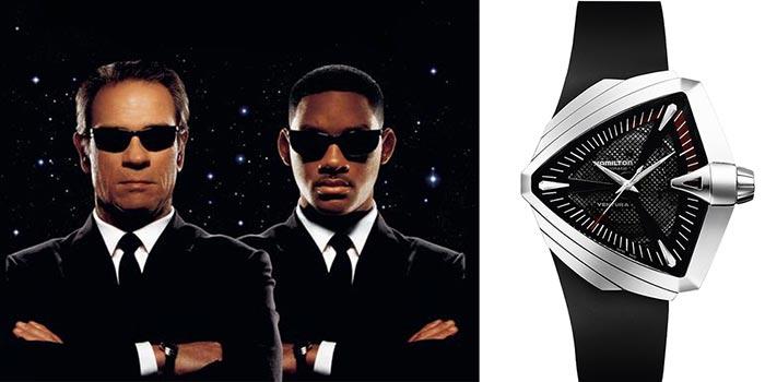 Hombres con traje negro, camisa blanca y lentes negros y a lado un reloj con correas negras y detalles en plateado