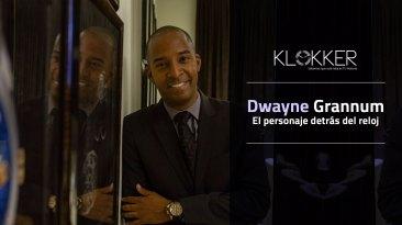 Dwayne Grannum recargado en la pared con saco y corbata en negro y camisa azul