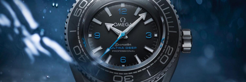 Reloj Omega con correas azules y caratula en color gris con detalles en color negro y azul dentro del agua
