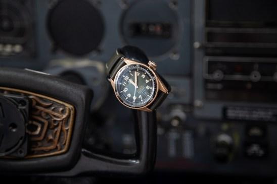 Reloj con correas negras y caratula en color dorado con detalles en negro y blanco sobre el volante de un avión