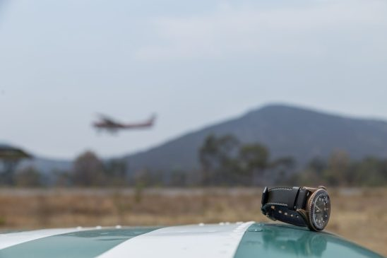 Reloj con correas negras y caratula dorada sobre el ala de un avión y al fondo un avión despegando