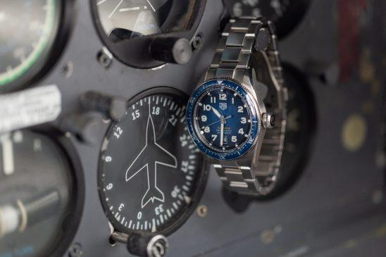 Reloj plateado con caratula azul colgando de un boton de una maquinaria de avión