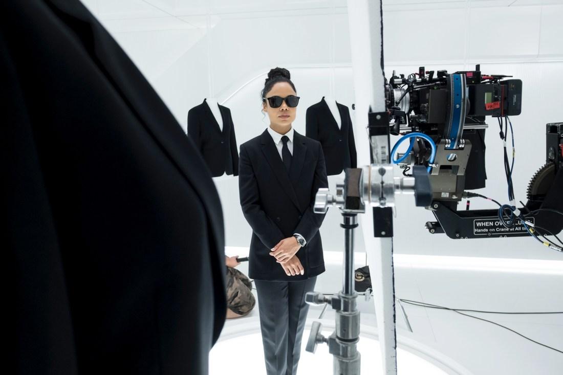 Tessa Thomspon con traje negro y camisa blanca con lentes negros y cabello recogido