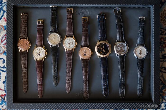 Colección de relojes con correas en color café, negro y azul marino sobre una caja en color azul