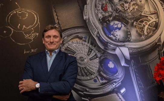 Stephen Forsey con saco azul marino y camisa azul claro y al fondo la imagen de un reloj