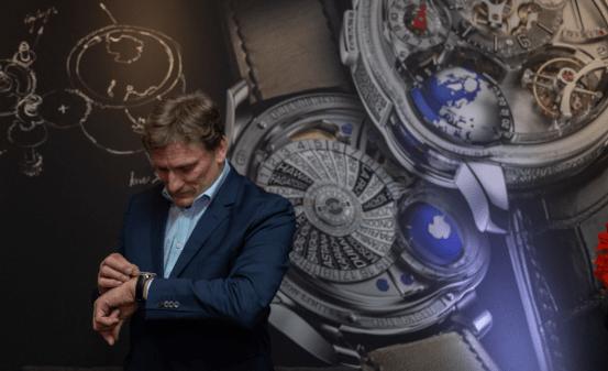 Stephen Forsey con saco azul marino y camisa azul claro agachado mirando su reloj
