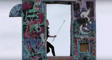 Tania Tare con un palo de golf detrás de un arco con grafitis