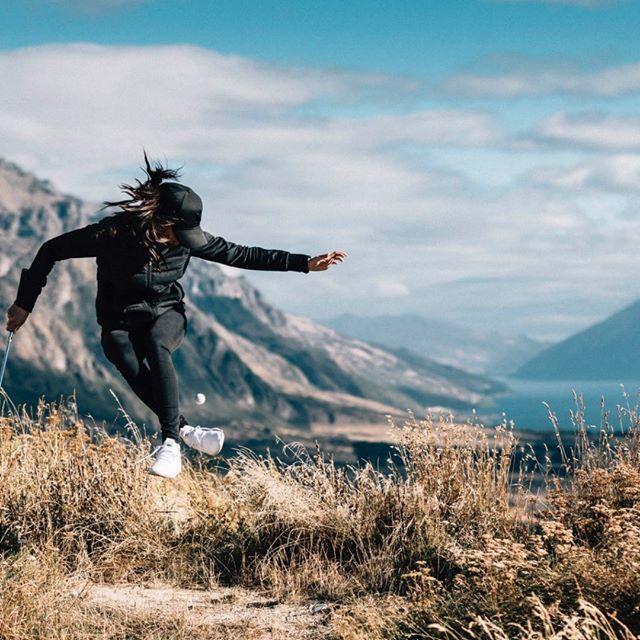 Tania con pantalón, chamarra y gorra negra con tenis blancos saltando en medio de montañas