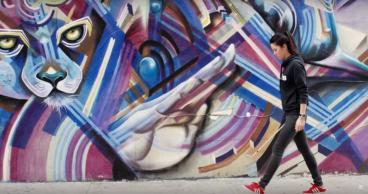Tania Tare con pantalón y sudadera negra con tenis rojos caminando