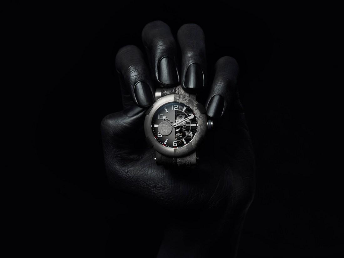 Mano sosteniendo el reloj The Joker en blanco y negro