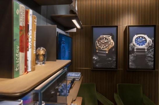 Cuadros de relojes colgados en la pared y a lado repisas con artículos