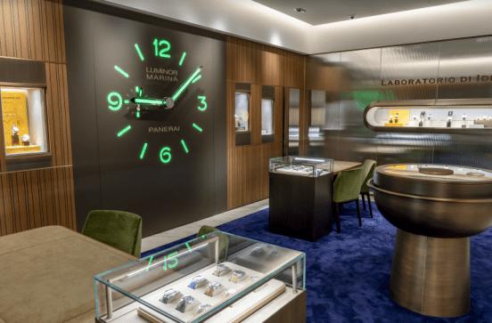 Interior de la boutique Panerai con un grande reloj en la pared, alfombra azul y vitrinas