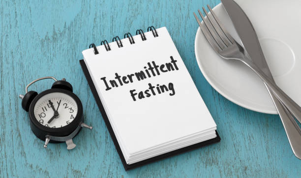 Intermittent fasting word on notepad with clock, fork and knife on white plate, weight loss and diet concept. Benefits of fasting.