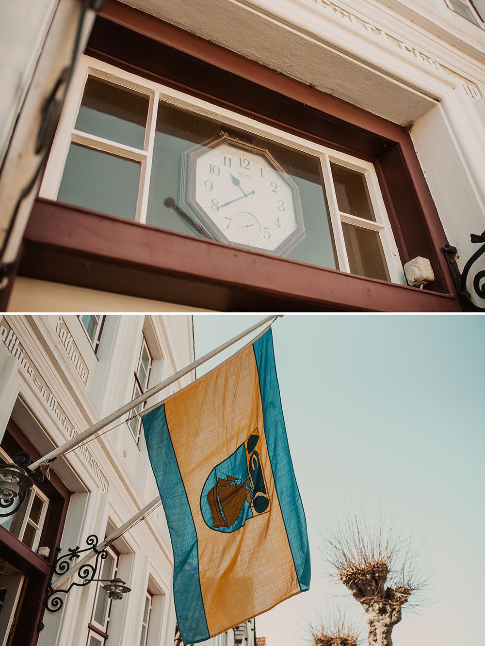 Fahne und Uhr im Eingang des Rathaus Arnis