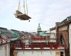 De torenkraan hijst het stuk van de dakconstructie uit de patio en over het gebouw. Foto: Karin Borghouts