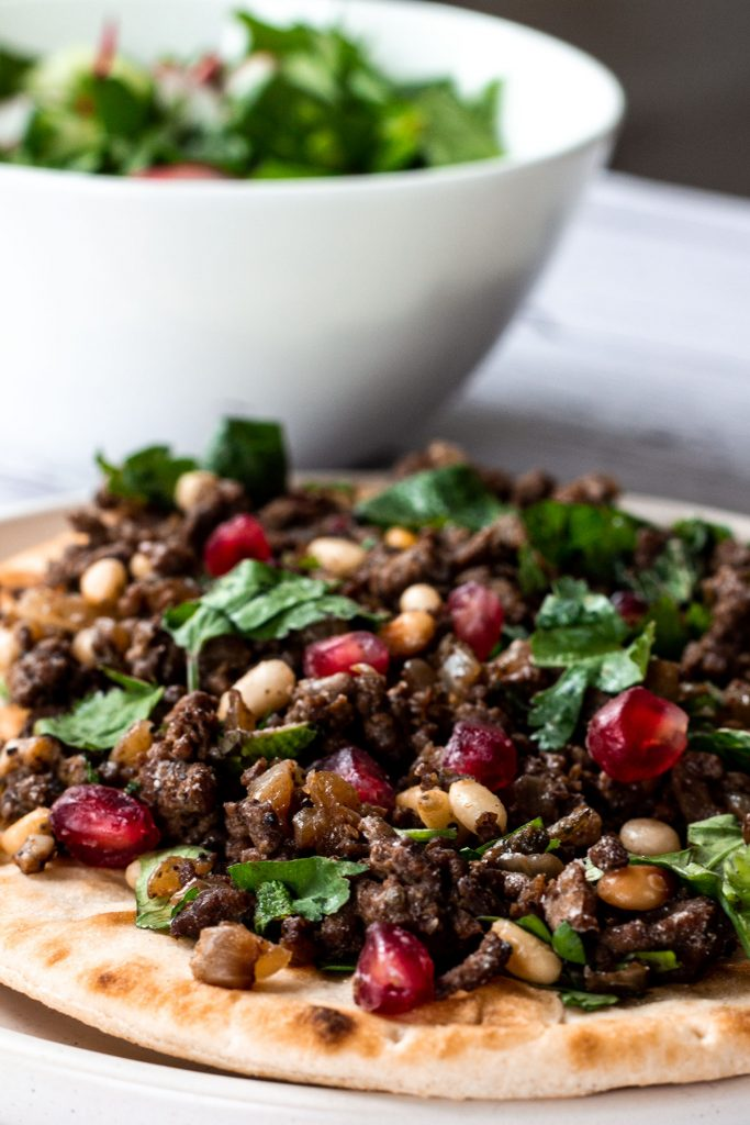 lamb mince flatbread with salad bowl in the background