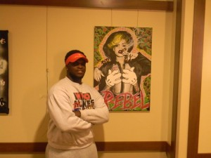 """Thanks to his artistic prowess, Braylin Robinson has become a popular figure within the Pace community. Here, he stands with one of his portraits, which he named """"Rude Boy"""". Photo by Jordan Harris."""