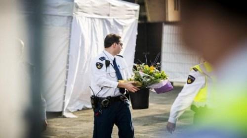 Een agent zet bloemen neer bij juwelier Goldies ©ANP