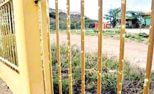 Het hek om het terrein waar zowel de huisartsenpraktijk als het meetstation op gevestigd is. De groene aanslag steekt af tegen de oorspronkelijk witte ondergrond. De overheid heeft meermaals tijdens zittingen gesteld 'geen verergering van de omstandigheden over de afgelopen periode te hebben waargenomen.' | Foto Ken Wong