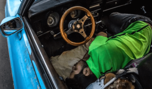 A man sleeps in his car at dawn outside a car-battery shop in Caracas, Venezuela, on Sept. 11, 2015. He was one of more than 80 drivers lined up overnight to buy a battery from the limited supply the next day