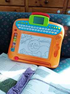 Child's magnetic drawing pad with blog name and logo drawn on it