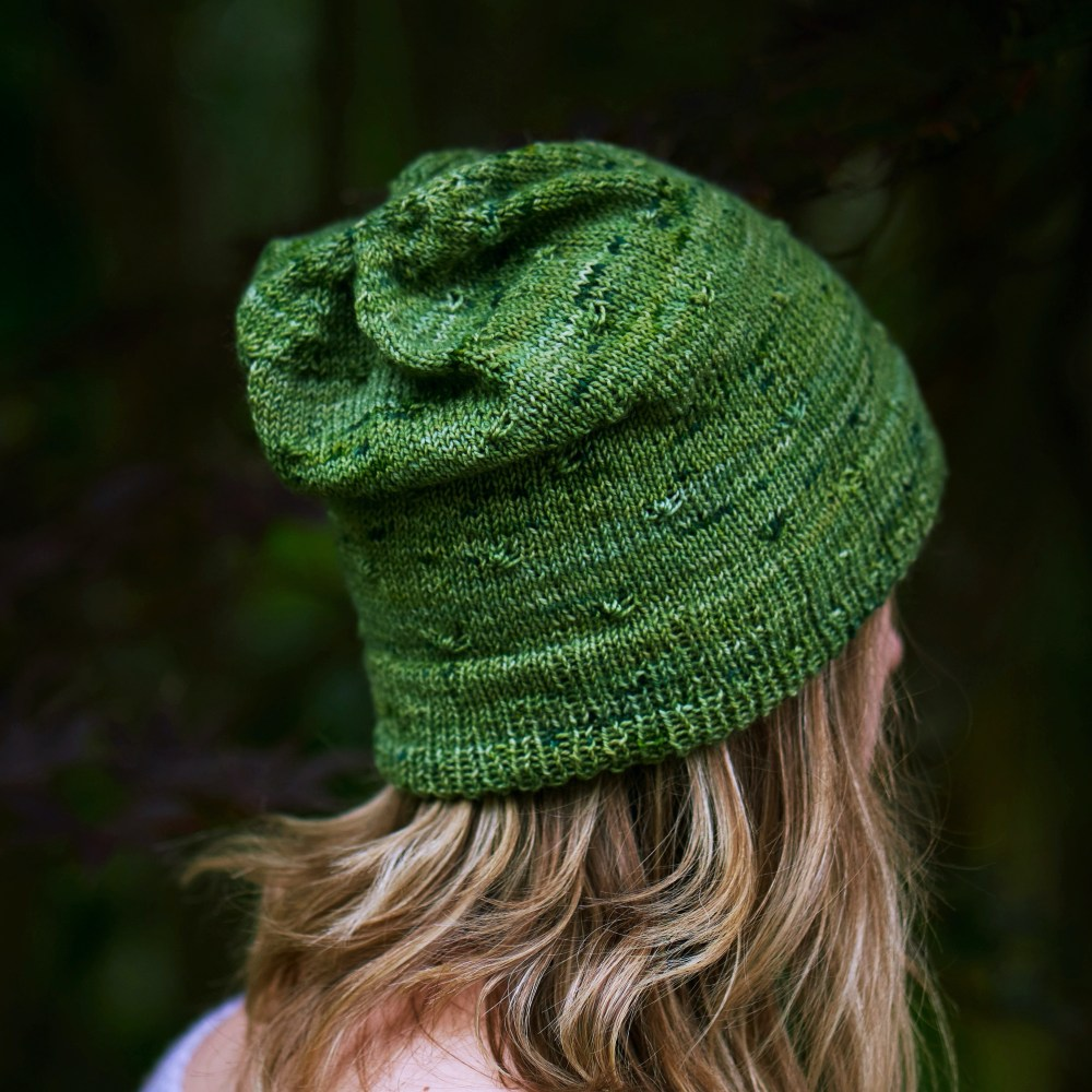 A deep medium green handknit slouchy hat with staggered knot stitches